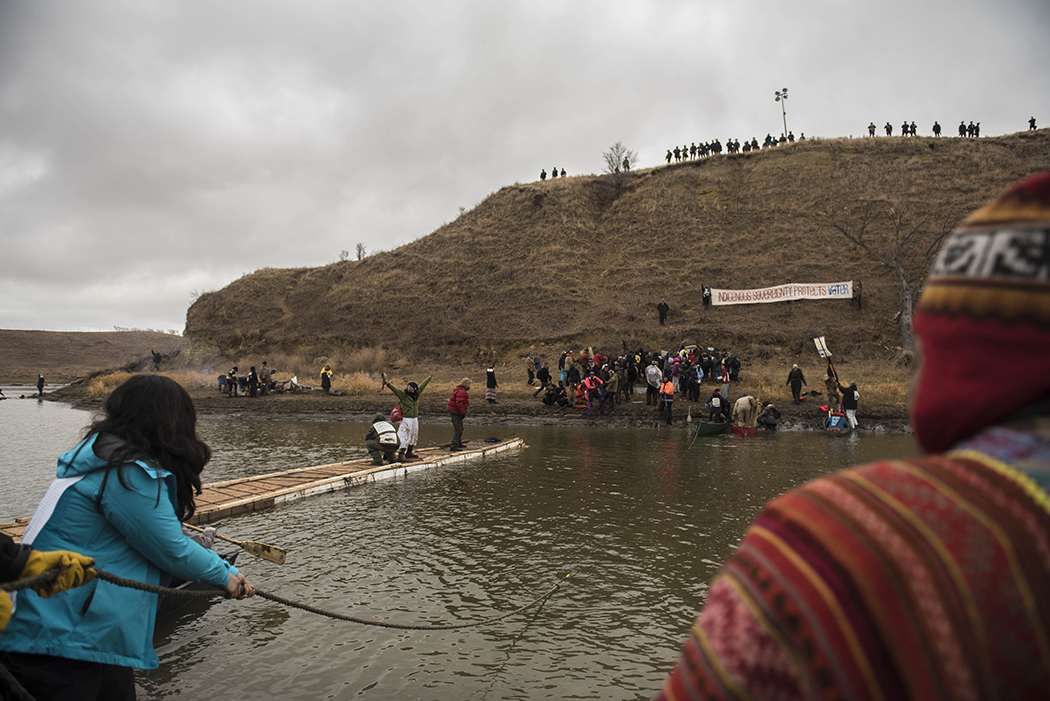 Police wait on top of Turtle Island Thanksgiving Day as water protectors travel across first with canoes and then with their rudimentary bridge.